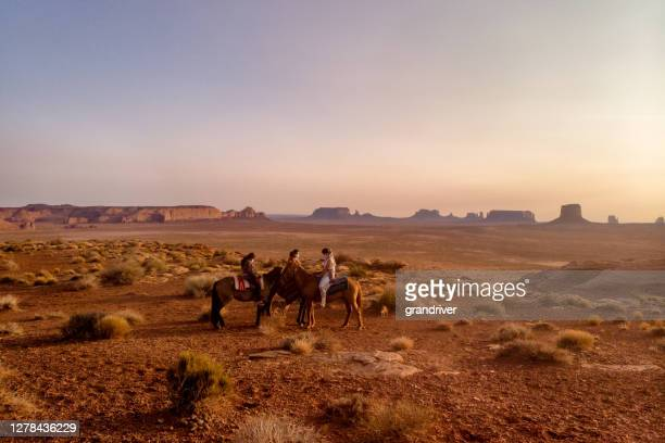 three teenage navajo people, one boy and two girls riding horseback through the desert near monument valley tribal park in northern arizona at sunset - cherokee culture stock pictures, royalty-free photos & images