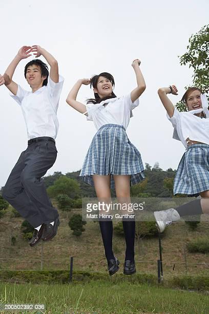 Three teenage (15-18) students in school uniforms jumping in midair