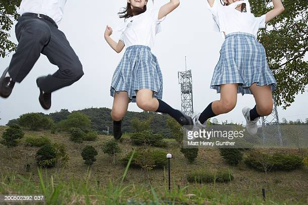 Three teenage (15-18) students jumping in midair, low section