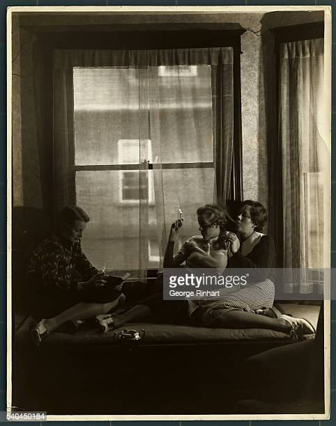 Three teenaged girls passing the time smoking cigarettes They are sitting by a window and one of the girls is reading a book while her friends look on
