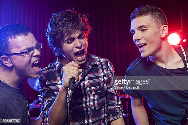 Three teenager singing into a microphone on stage