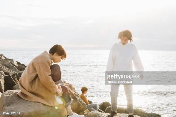 three teenagers are talking on a rock. - yusuke nishizawa bildbanksfoton och bilder