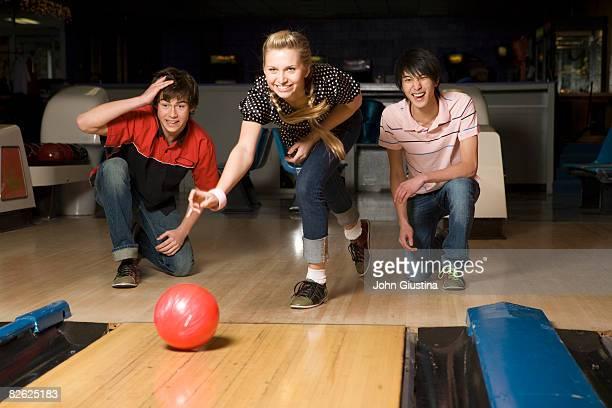Three teenagers (15-17) bowling.