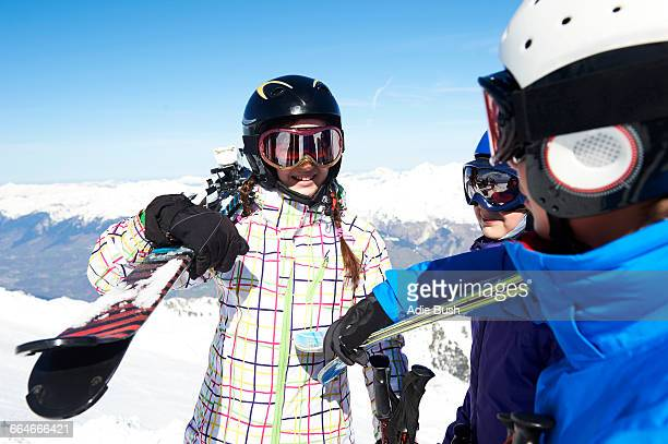 Three teenagers carrying skis