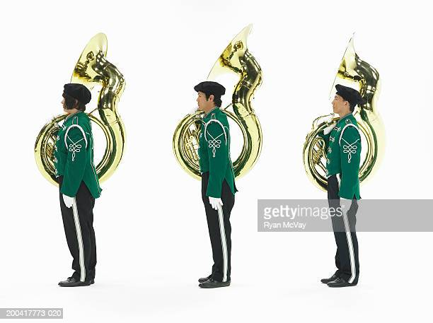 Three teenagers (14-17) in band uniforms carrying tubas, side view