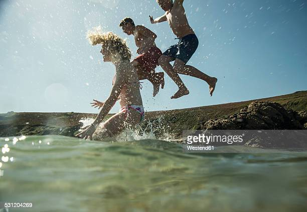 Three teenagers jumping into the sea