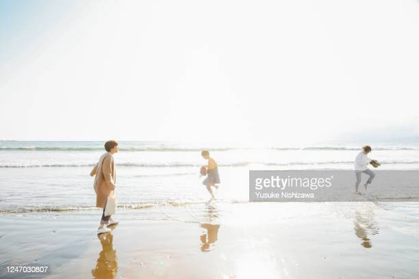 three teenagers playing on the water's edge - yusuke nishizawa stock pictures, royalty-free photos & images