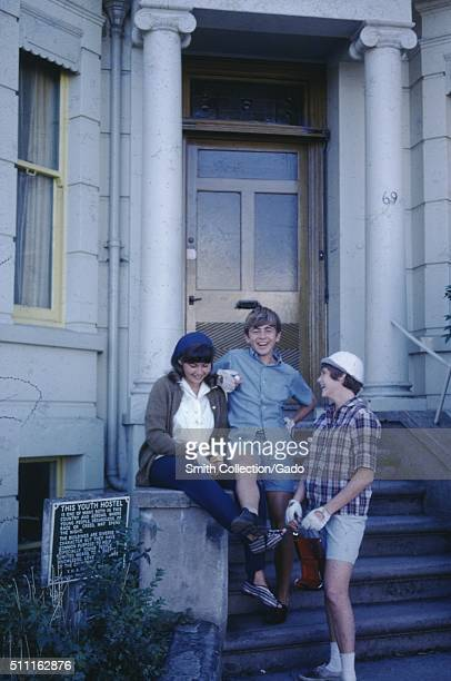 Three teenagers relaxing talking and smiling on the stone stairs of a youth hostel wearing biking gloves 1960