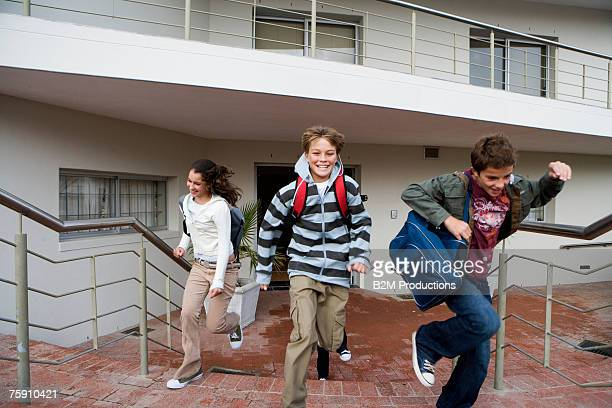 three teenagers (13-15 years) running from school, smiling - 14 15 years stock pictures, royalty-free photos & images
