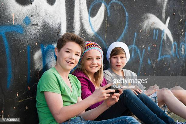 Three teenagers sitting in front of a graffiti wall