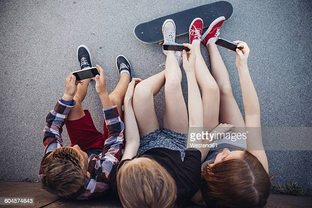 Three teenagers sitting outdoors with smartphones and skateboard