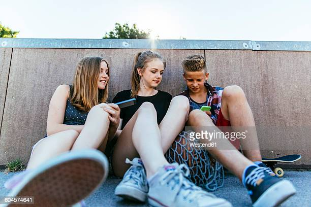 Three teenagers sitting outdoors with smartphones