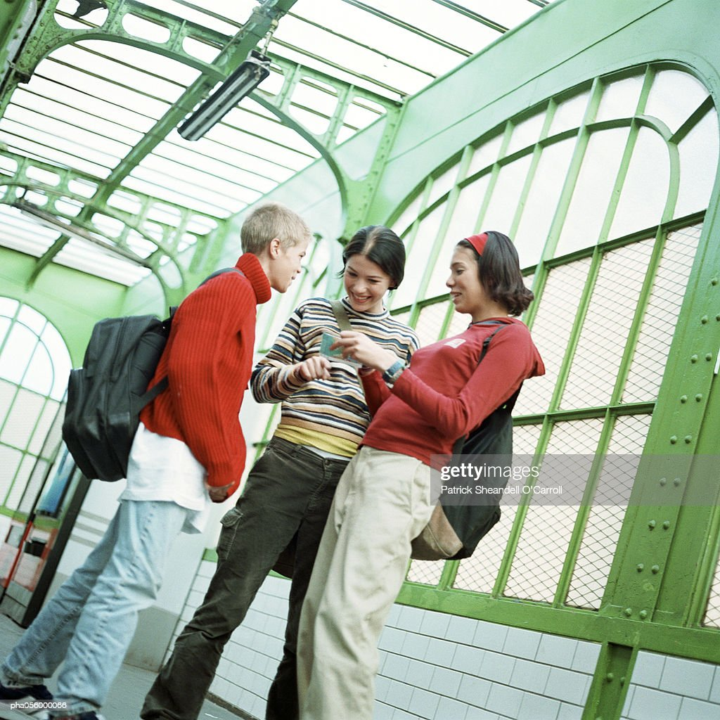 Three teenagers standing in a station : Stockfoto