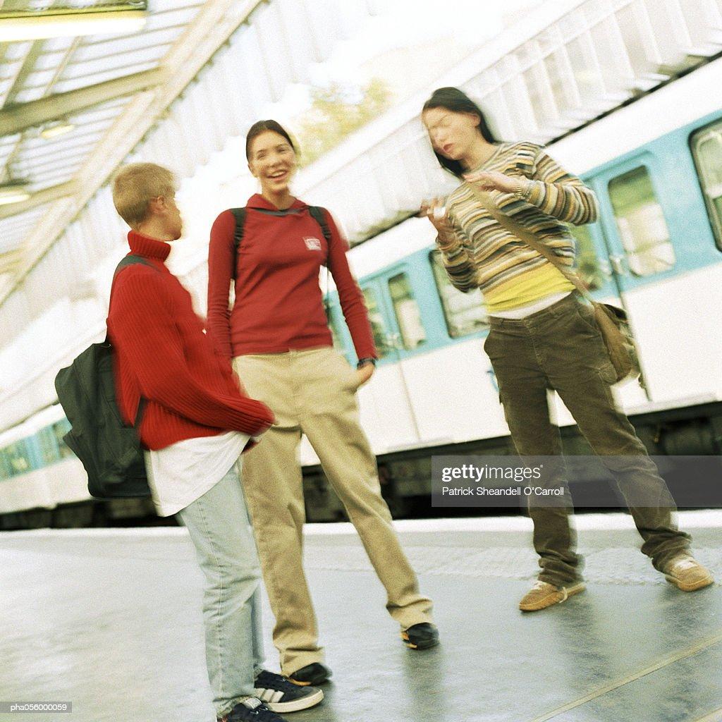 Three teenagers standing on subway platform, blurred : Stockfoto