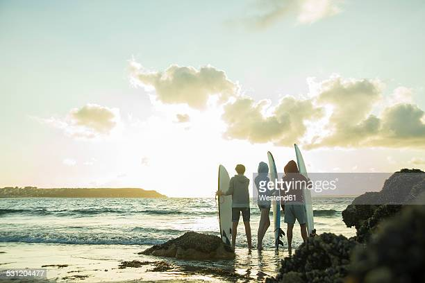 Three teenagers standing on the beach with their surfboards looking at horizon