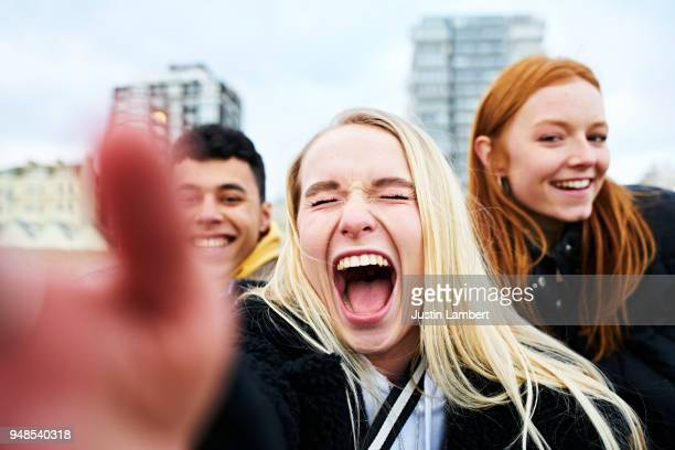 three teenagers taking a selfie on their mobile phone taken from the phone's perspective with hand in view of the camera. two friends lean in from both sides with main woman smiling and laughing openly while the picture is taken, all smiling at camera - city life stock pictures, royalty-free photos & images