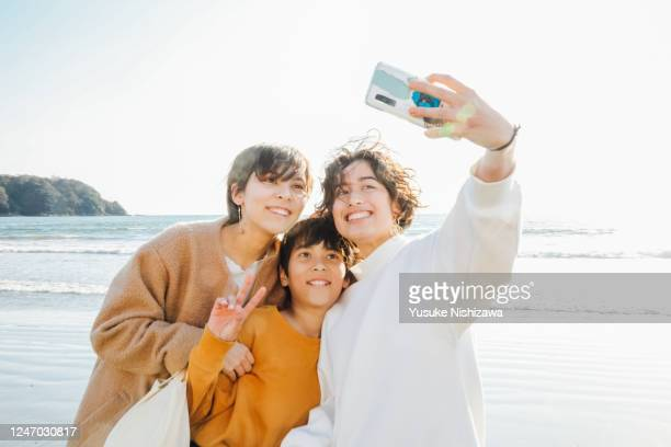 three teenagers taking selfies on the side of the waves - yusuke nishizawa stock pictures, royalty-free photos & images