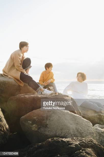 three teenagers talking on a rock. - yusuke nishizawa stock pictures, royalty-free photos & images