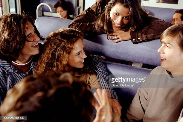 three teenagers (16--17 years) talking to young woman on train - 25 29 years stock pictures, royalty-free photos & images
