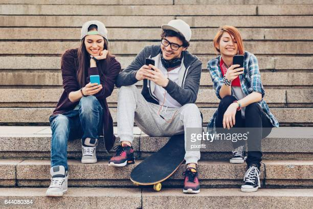 Three teenagers text messaging on a staircase