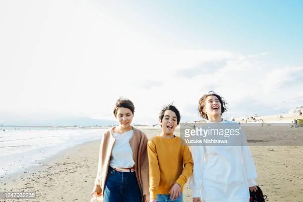 three teenagers walking together on sandy beach - travel ストックフォトと画像