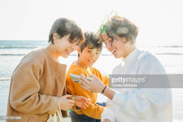 three teenagers watching their phones on the side of the waves - yusuke nishizawa stock pictures, royalty-free photos & images