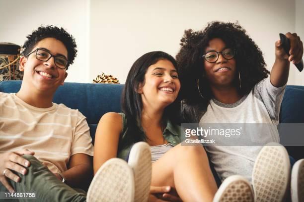 três adolescentes que prestam atenção à tevê junto e que têm o divertimento - 18 19 anos - fotografias e filmes do acervo