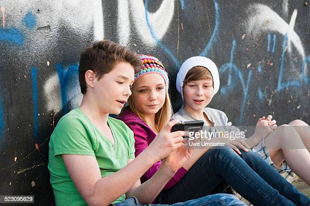 Three teenagers with a Smartphone sitting in front of a wall with graffiti