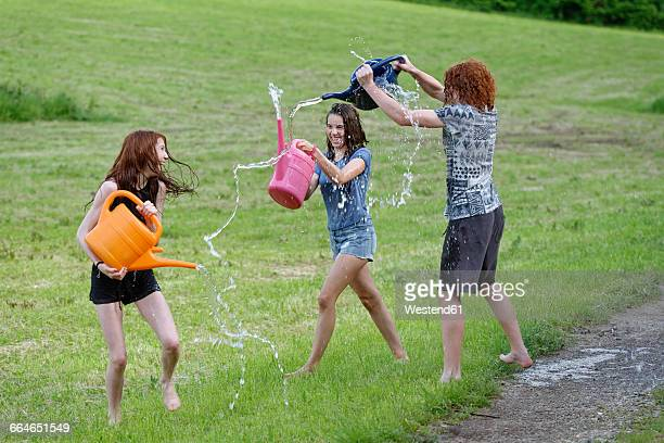 Three teenagers with watering cans splashing with water