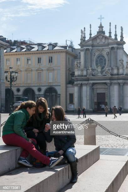 Three teens gather in piazza