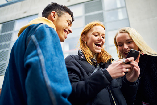 Three teens laughing and joking while looking at their phone - gettyimageskorea