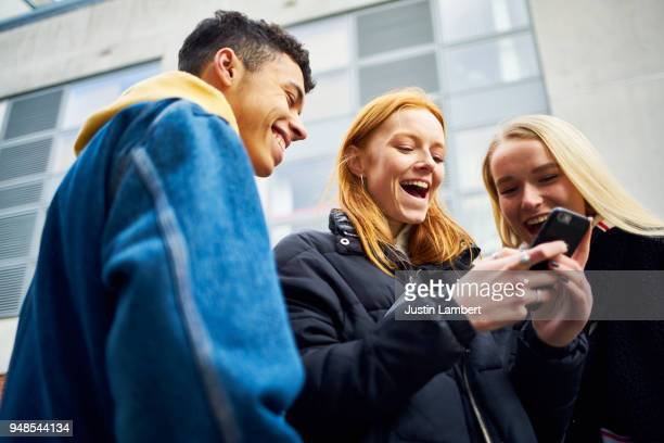 three teens laughing and joking while looking at their phone - adolescence stock pictures, royalty-free photos & images