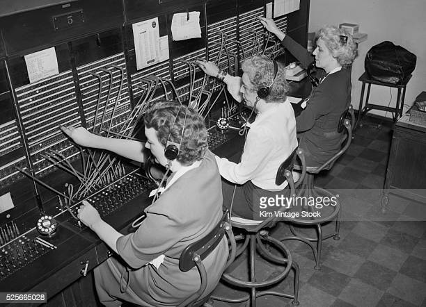Three telephone operators connect and route calls from their modern switchboard in midcentury Chicago