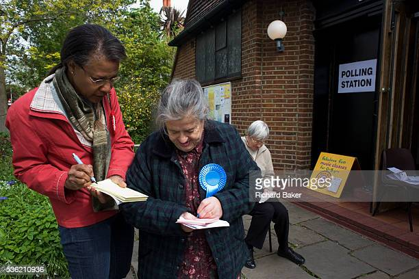 Three tellers from the main political parties check the addresses of voters in St Barnabas Parish Church Dulwich Village SE21 that serves as a...
