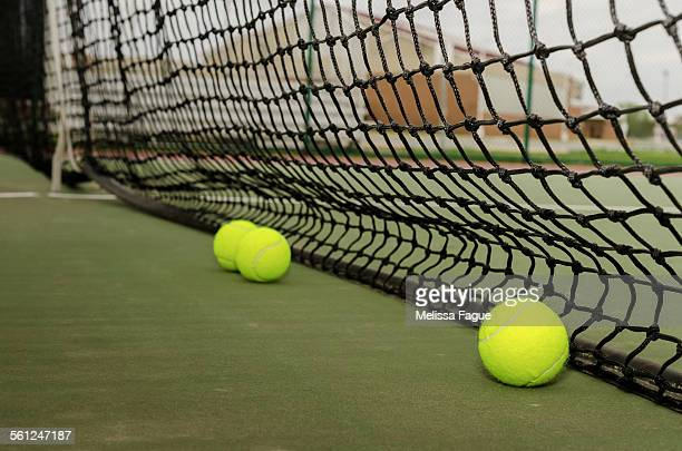 Three tennis balls near net