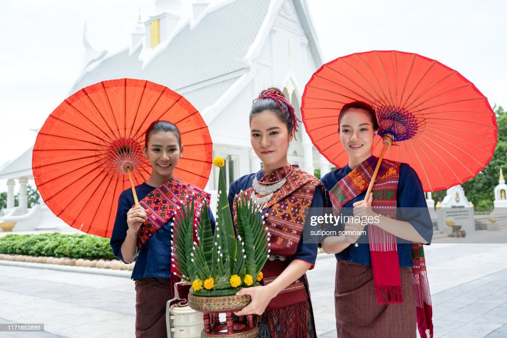 Three Thai girls dressed in traditional Isan traditional dress to go to the temple. : Stock Photo