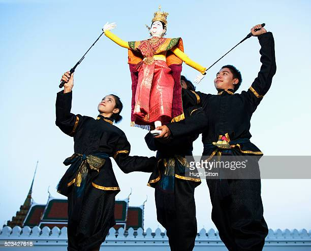 three thai puppet dancers with a puppet outside the grand palace, bangkok, thailand - hugh sitton 個照片及圖片檔