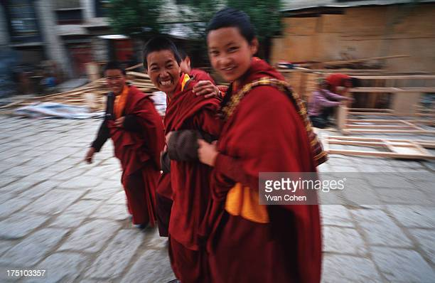 Three Tibetan nuns smile as they walk along the cobbled street that leads away from the Kumbum Stupa at Pelkor Chode Monastery in the town of...
