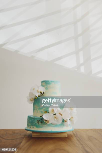 three tiered turquoise ombre wedding cake with white orchids