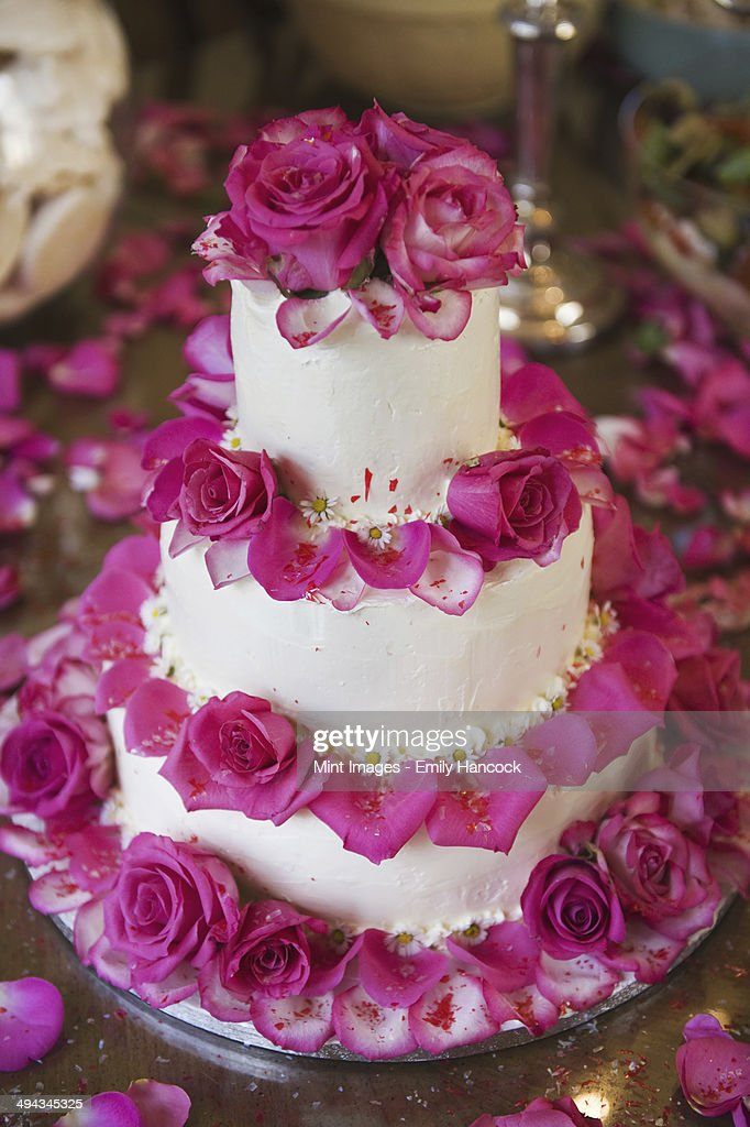wedding cake decorated with rose petals a three tiered wedding cake covered in white frosting and 22365