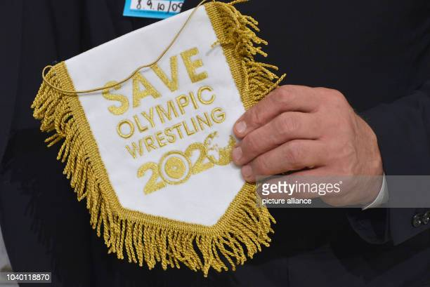 Three times Olympic gold medalist Alexander Karelin from Russia holds a pennant after a press conference at the125th IOC Session at the Hilton hotel...
