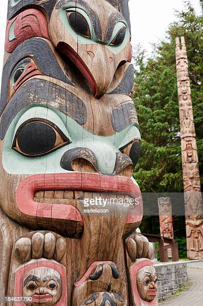 three totem poles - totem pole stock photos and pictures