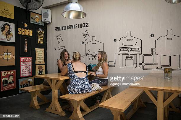 Three tourist chat in Stark Beer house on Legian Street on April 16 2015 in Kuta Bali Indonesia Indonesia on April 16 banned small retailers from...