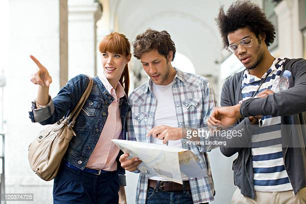 Three tourist friends looking at map in city.
