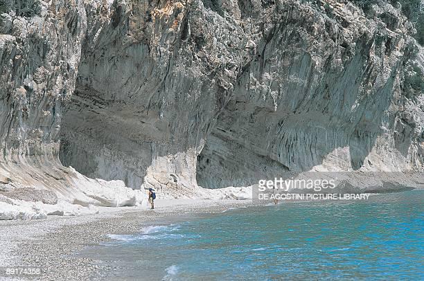 Three tourists standing on the beach Cala Luna Gennargentu National Park Gulf Of Orosei Sardinia Italy