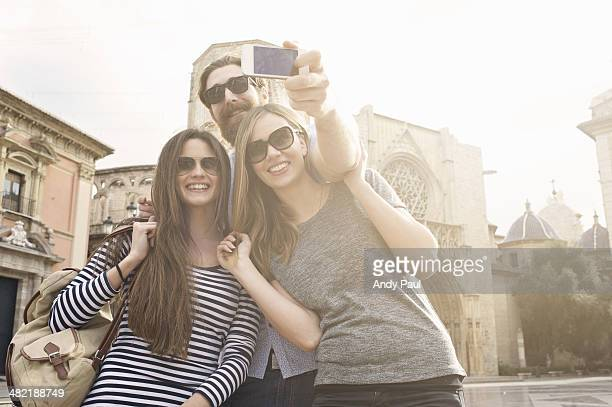 Three tourists taking self portrait, Plaza de la Virgen, Valencia, Spain