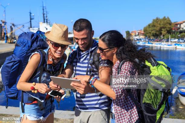 Three tourists using digital tablet on street