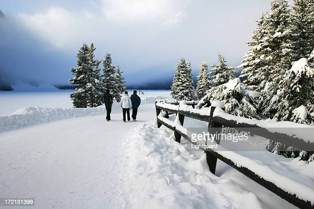 Three tourists walk along snow covered path at Lake Louise