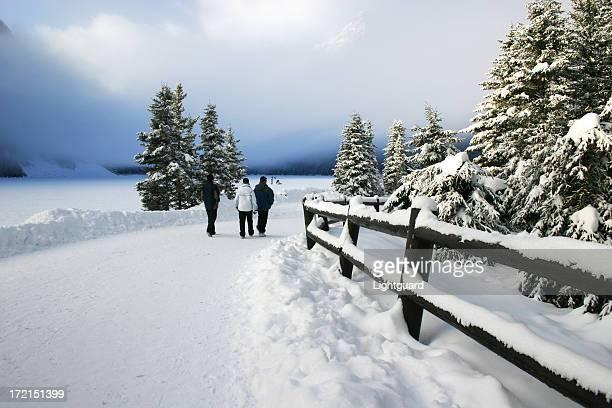 Trois touristes marcher dans la neige recouvert chemin du Lac Louise