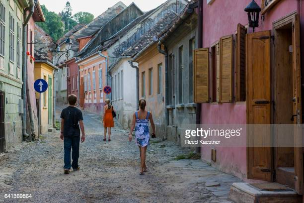 Three tourists walk along the colorful old houses in the back roads of Sighisoara, Romania
